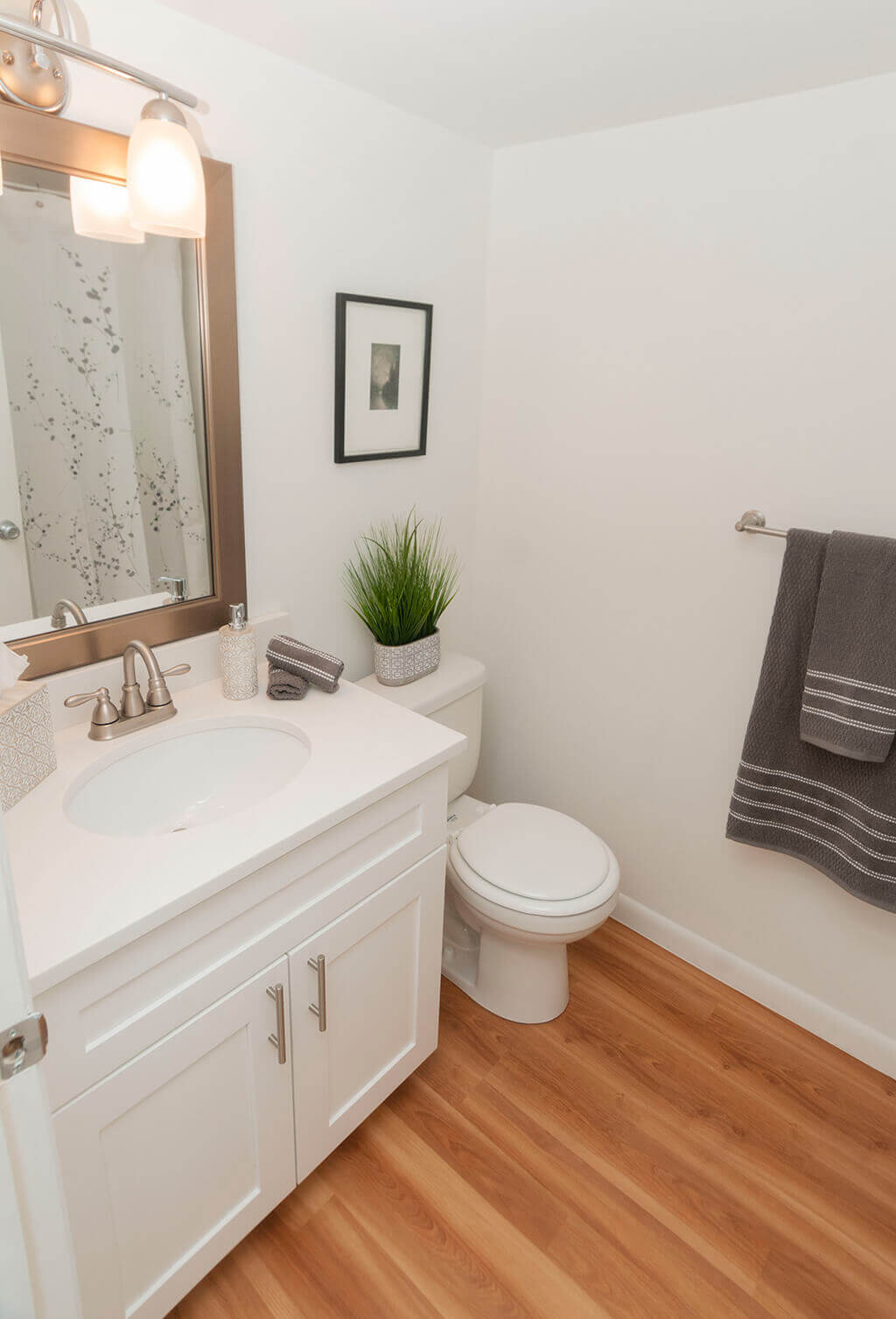 Renovated bathroom with white vanity cabinets